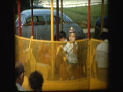 50's family watches kids on traveling carnival ride spinning - stock footage