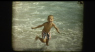 Young boy enters ocean Stock Footage