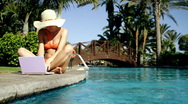 Woman working on laptop by the pool Stock Footage