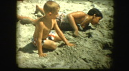Happy kids dig in sand at beach and young girl sticks her tongue out Stock Footage