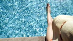 Woman with a hat relaxing at the pool, top view Stock Footage