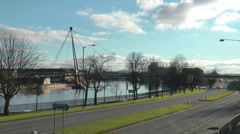 Riverside road with traffic, foot bridge across river and modern office blocks Stock Footage