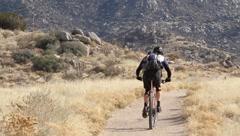 Mountain bikers in desert Stock Footage