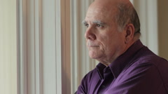 Senior man looking out window sad Stock Footage