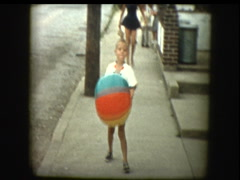 Cute little boy with beach ball in street Stock Footage
