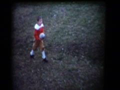 Young boy in football uniform tossing football - stock footage