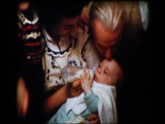 Grandparents and brother watch Mom feeding infant baby bottle Stock Footage
