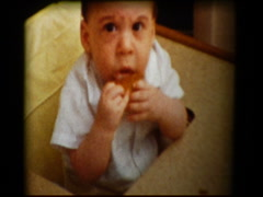Baby boy eating in high chair Stock Footage