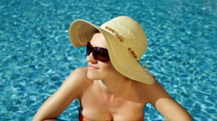 Beautiful sexy happy woman in sunglasses standing in swimming pool Stock Footage