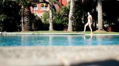 Beautiful sexi young woman in bikini walking by the pool  Stock Footage