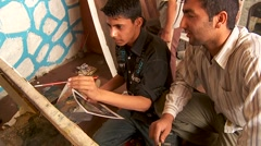 Two boys work on a painting at an art school in Kabul, Afghanistan. Stock Footage