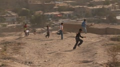 Boys play on the hillsides flying kites in modern Kabul, Afghanistan. - stock footage