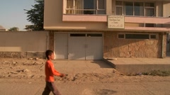 A boy flies a kite ion front of a residential building in Kabul, Afghanistan. Stock Footage