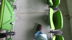 Man is passing by the rows of seats at the stadium. Stock Footage