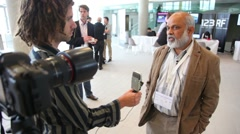Man is being interviewed by a journalist on CEPIC Congress Stock Footage
