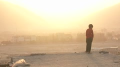 A boy looks out over Kabul Afghanistan during a dust storm. Stock Footage