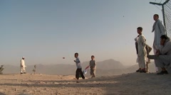 Kids chase and play with kites in an empty lot in kabul, Afghanistan. Stock Footage