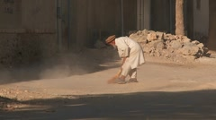 An old man sweeps the street and clears stones and rocks in Kabul, Afghanistan. Stock Footage