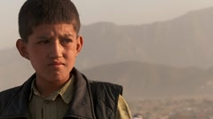 Close up portrait of boy's face as friends fly kites in an empty lot in Kabul, Stock Footage