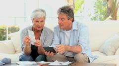 Elderly couple calculating their bills Stock Footage