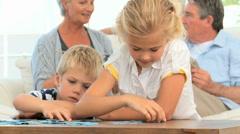 Lapset palapelin kokoamiseen, kun heidän isovanhemmista puhuvat Arkistovideo