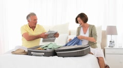 Mature couple leaving for vacacion and packing Stock Footage