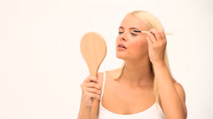 Blond woman putting on make up Stock Footage