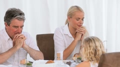Family praying before dinner - stock footage