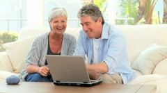 Senior couple looking at a computer Stock Footage