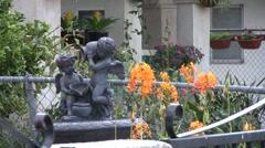 Orange flowers with garden sculpture Stock Footage