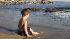 A young boy playing on the beach Stock Footage