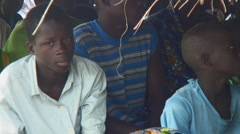 Africa: Bored children sitting in crowd Stock Footage