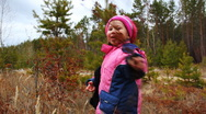 Little girl walking and playing outdoor in the autumn forest Stock Footage