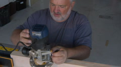 Handyman Carpenter turns on Router Stock Footage