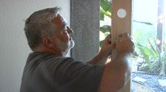Handyman installs door knob Stock Footage