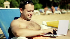 Attractive man uses his laptop while tanning poolside  Stock Footage