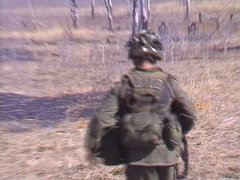 Military, soldier runs, drops and fire rifle, fire flames from grass fire Stock Footage