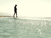 A dark silhouette image of man walking along a beach Stock Footage