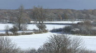 Slow zoom out from snow covered fields, trees. Stock Footage
