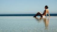 A beautiful woman sunbathing by the sea Stock Footage