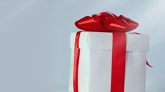 Rotating gift in white box with red ribbon Stock Footage