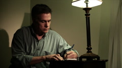 Close man writing at a small desk Stock Footage
