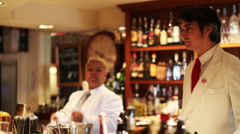 Male and female cocktail waiter in a classic looking cocktail Stock Footage