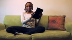 Young adult woman on couch with iPad and cell Phone Stock Footage