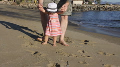 Baby girl walking on the beach with daddy - stock footage