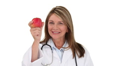 Ederly nurse showing us an apple Stock Footage