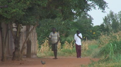 Africa: Two teens walking dusty street Stock Footage