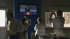 Journalists watch President Obama on television at the G8 media camp - stock footage