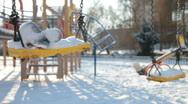 Empty swings in winter snow Stock Footage