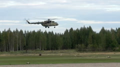 military helicopter landing with cargo near forest - stock footage
